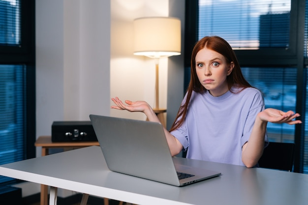 夜遅くに窓の近くのホームオフィスの机に座って、カメラを見て、ラップトップコンピュータの問題に混乱している欲求不満の若い女性。