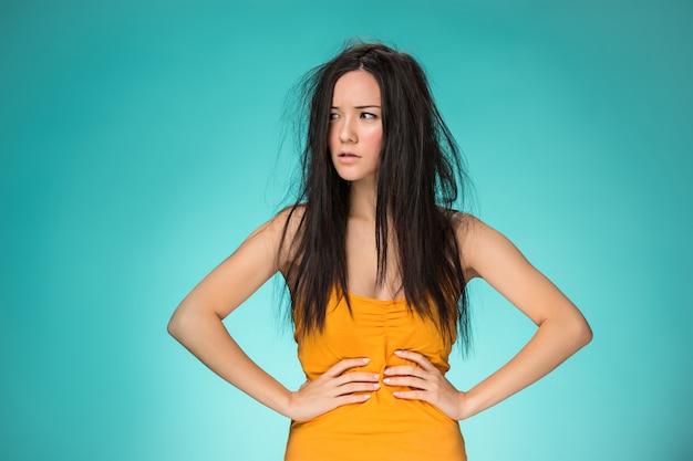 悪い髪を持つ欲求不満の若い女性