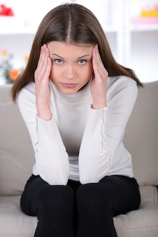 Frustrated young woman holding head in hands.