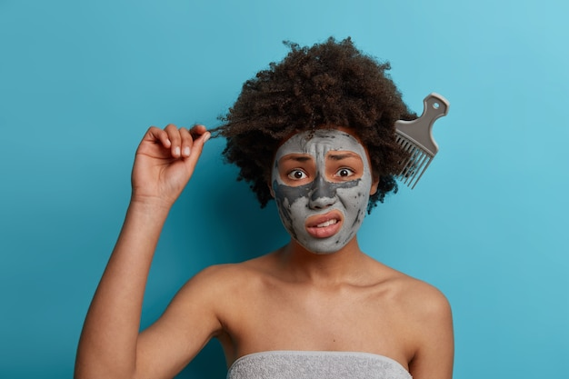 Frustrated young woman holds curl, stands with comb tangled in frizzy hair, has puzzled face, wears beauty natural mask for refreshing, prepares for date. hair care, spa treatments and hygiene concept