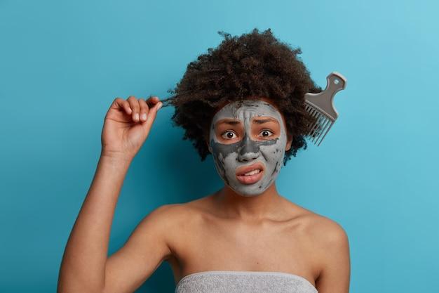 좌절 한 젊은 여성이 컬을 잡고 곱슬 머리에 얽힌 빗으로 서서 얼굴을 어리둥절하게 만들고 상쾌한 미용 천연 마스크를 쓰고 데이트를 준비합니다. 헤어 케어, 스파 트리트먼트 및 위생 개념