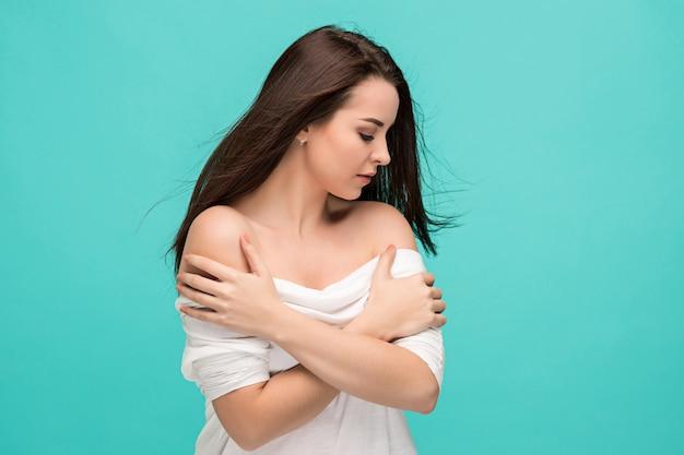 Разочарованный молодая женщина позирует на синем