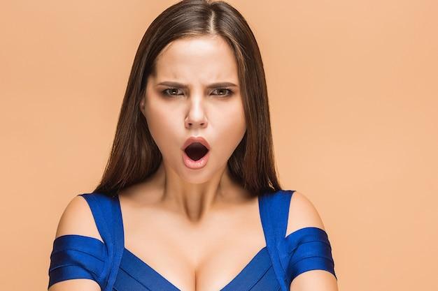 Giovane donna frustrata che grida sul fondo marrone dello studio
