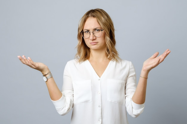 Frustrated young woman shrugs shoulders with her arms out isolated