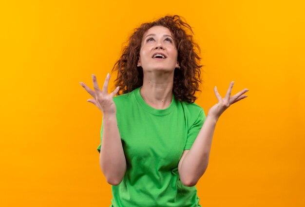 Giovane donna frustrata con capelli ricci corti in maglietta verde che osserva in su con le mani alzate