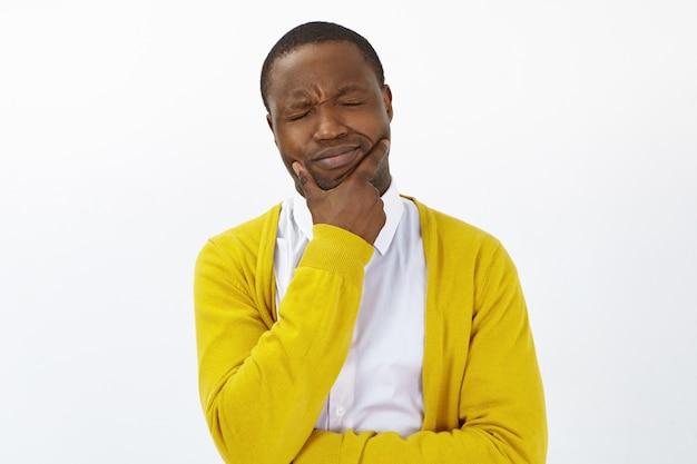 Разочарованный молодой взволнованный мужчина афроамериканца, держащий руку на подбородке, испытывает ужасную зубную боль, закрывает глаза, имеет болезненно-страдальческий взгляд. люди, образ жизни, здоровье, болезни и боль