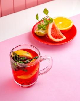 Frut te with lemon orange mint and grapefruit on table