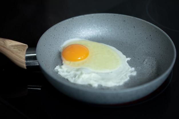 フライパンで卵を炒める朝食キッチンで簡単に調理
