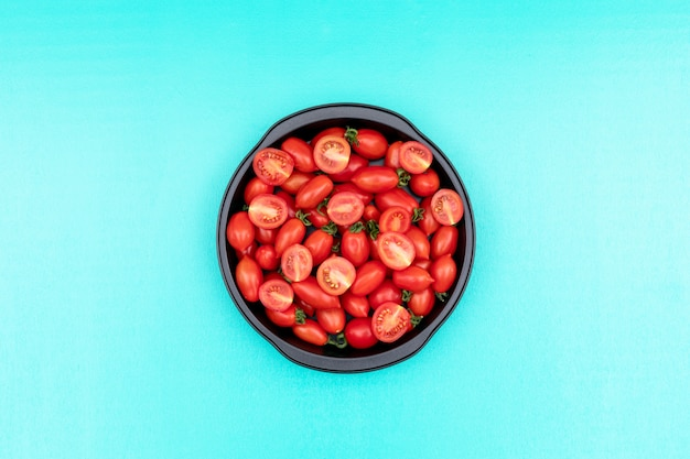 The fry pan filled with cherry tomatoes in center on light blue surface