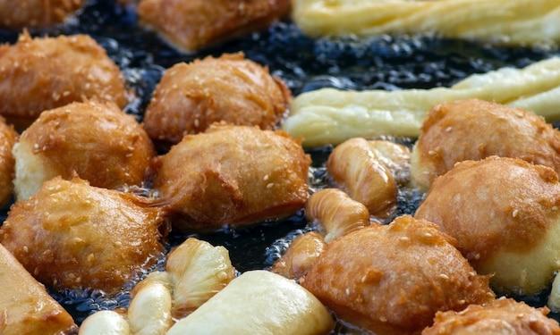 Жарка cakwe или cakue в горячем масле, популярная традиционная закуска из азии, вкусная уличная еда, избранный фокус.