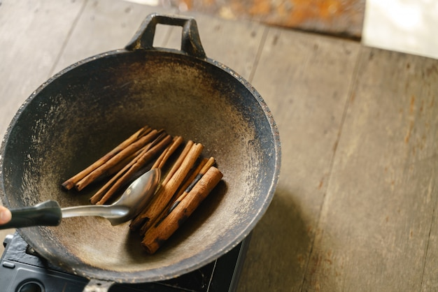 Frying cinnamon stick with pan over portable stove