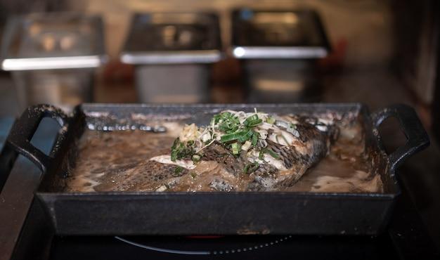 キッチンレストランの鋳鉄鍋で揚げ魚料理。グリドルの前菜台湾シーフードスタイル。台湾での夕食に美味しい健康食品