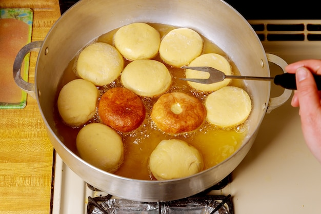 Frying and flipping round donuts in hot oil.