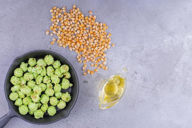 Padella contenente caramelle popcorn accompagnate da ingredienti per fare popcorn su fondo marmo. foto di alta qualità