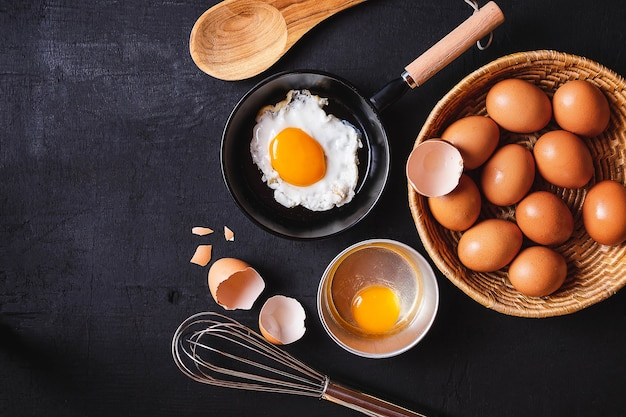 Frying pan in eggs and raw eggs on background