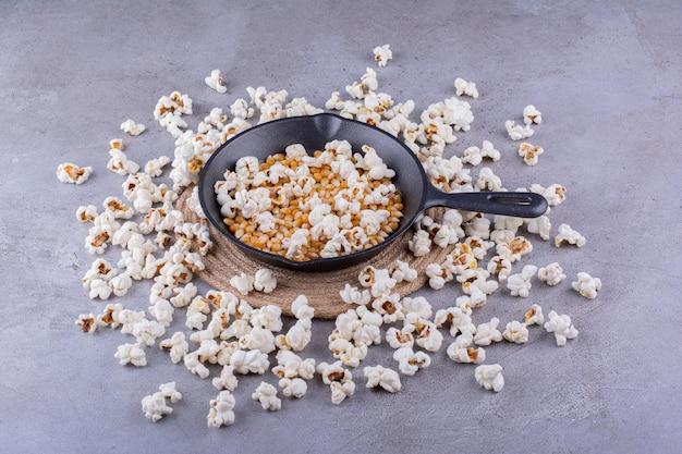 Сковорода с наполовину открытыми зернами кукурузы, окруженная грязным кружком попкорна на мраморном фоне. фото высокого качества