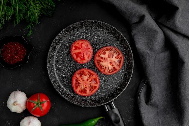 ニンニクフェンネルと黒いテーブルの上のスパイスとトマトのフライパン