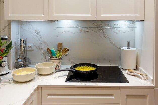 ポテトオムレツを調理するための沸騰油とガラスセラミックコンロのフライパン