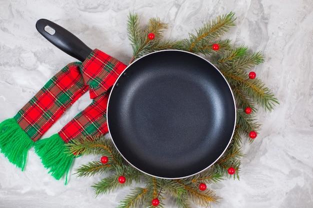 大理石のテーブルの上のクリスマスツリーの周りのフライパンまたはフライパン。上面図