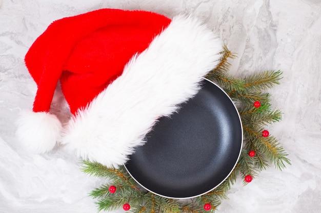 大理石のテーブルの大理石のテーブルの上のクリスマスの帽子とフライパンまたはフライパン。上面図。