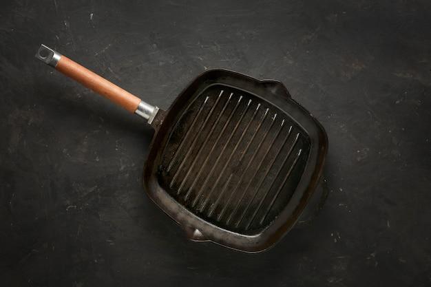 Сковорода на темном фоне бетона.