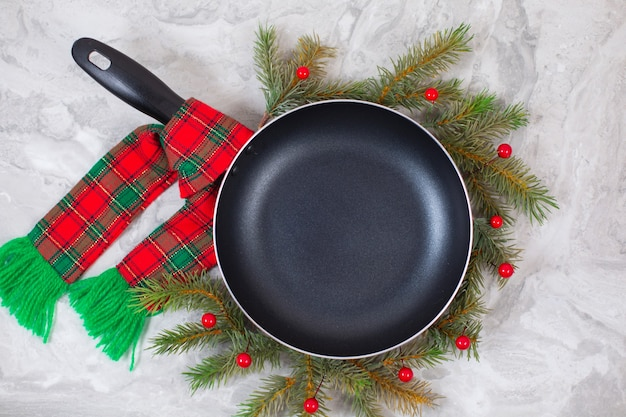 Frying pan or skillet around christmas tree on on marble table. top view