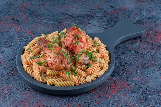 Una padella di maccheroni a spirale e carne di coscia di pollo