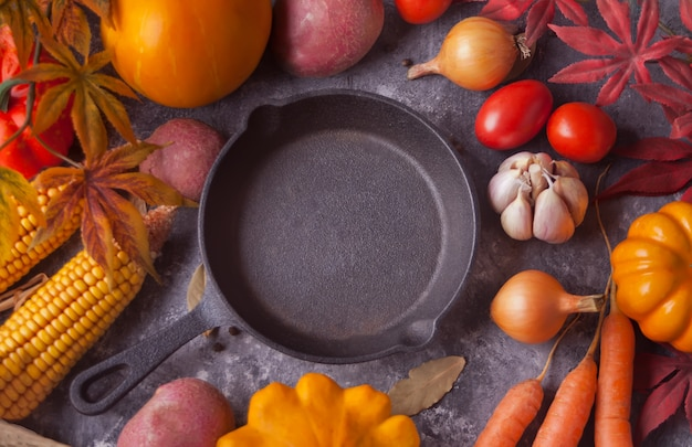 Frying pan with autumn leaves and vegetables on the black background