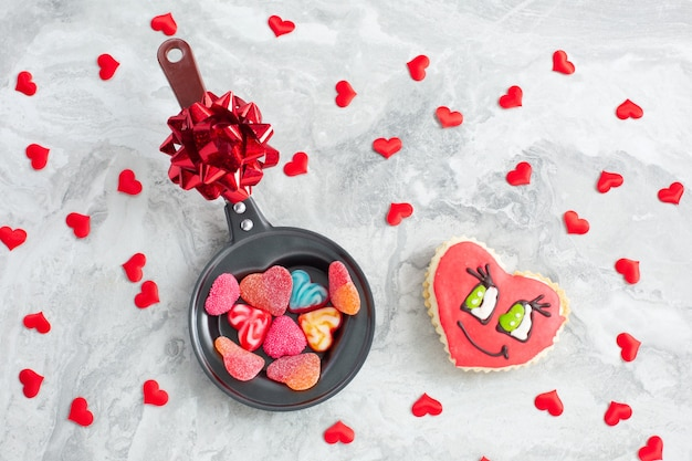 Frying pan with candies heart-shaped and cookies on festive