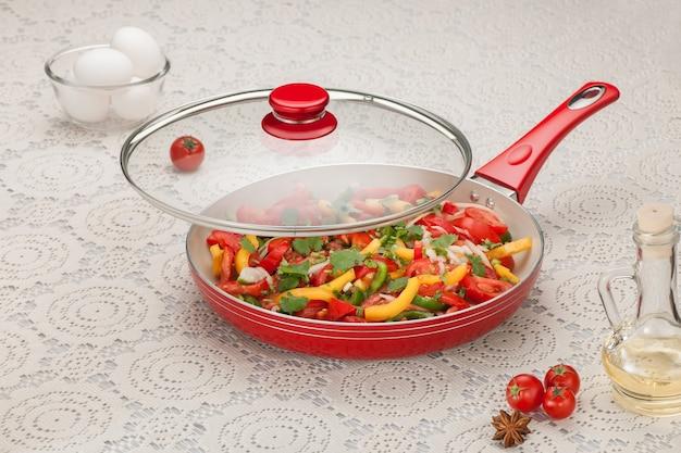 흰 냅킨에 다진 야채를 얹은 프라이팬 생 토마토와 계란 ahd 유리병