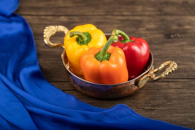 Сковорода с красочными болгарскими перцами на деревянном столе.
