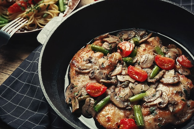 Сковорода с вкусной курицей марсала на столе