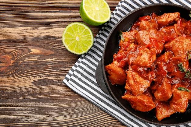 나무 테이블에 맛있는 치킨 티카 마살라를 넣은 프라이팬