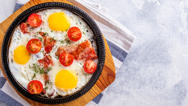 Сковорода с яйцом, беконом и помидорами. концепция завтрака. вид сверху. копировать пространство