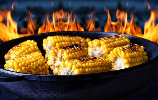 Сковорода с жареной кукурузой на огненной стене
