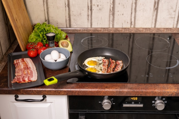 Frying pan with fried eggs and bacon on electric stove with fresh ripe tomatoes, avocado and lettuce near by in the kitchen