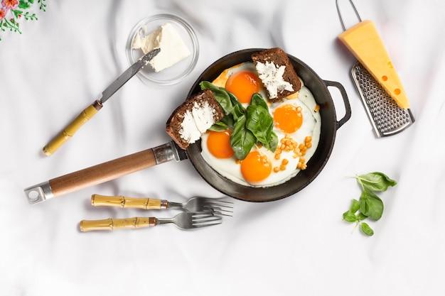 가벼운 공간에 튀긴 계란 프라이팬. 화이트 식탁보
