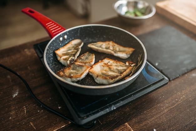 Сковорода с обжаренным филе рыбы, приготовление морепродуктов. ломтики морского окуня