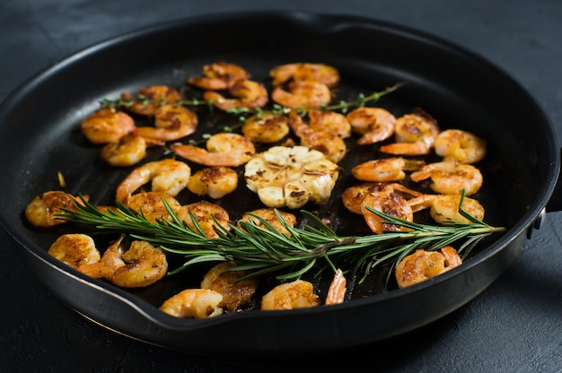 Frying pan with fried king prawns and sprigs of rosemary and thyme.