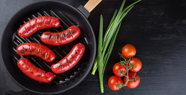 Frying pan with fried sausages and tomatoes with onions