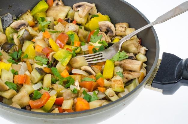 白地に旬の野菜とキノコの炒め物が入ったフライパン。