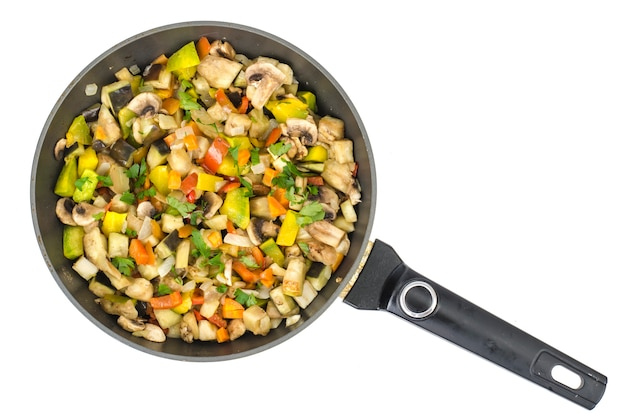 Frying pan with fried seasonal vegetables and mushrooms on white.