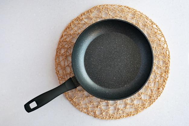 Frying pan with handle on woven anti-heat napkin