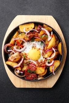 검은 콘크리트 바탕에 감자 고기와 계란 프라이팬