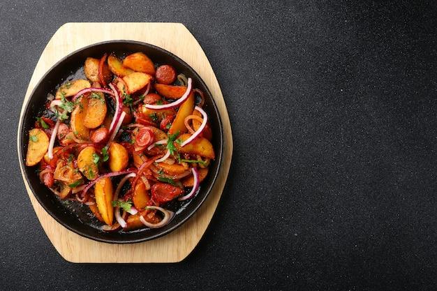 黒いコンクリートの背景にジャガイモの肉と玉ねぎとフライパン