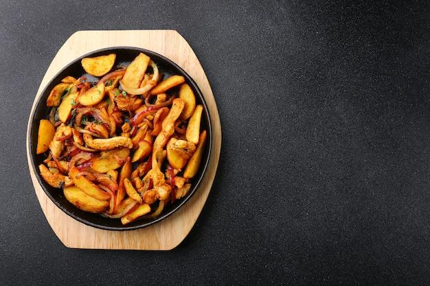 Сковорода с мясом картофеля и жареным луком на черном фоне бетона
