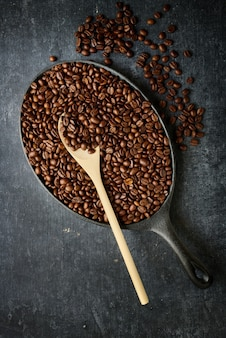 Frying pan with roasted coffee beans and wooden stirring spoon, top view