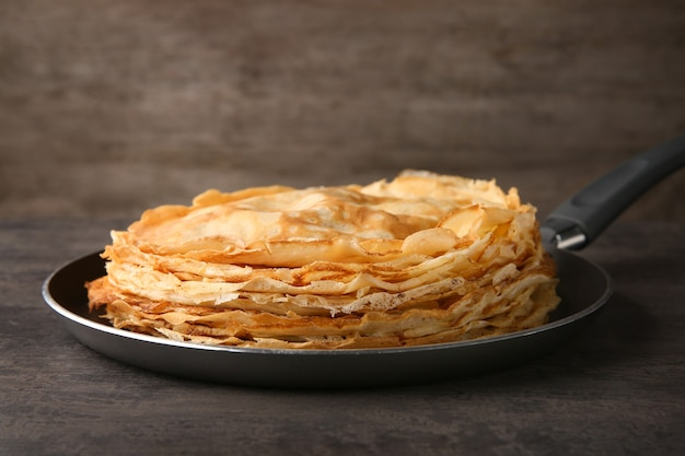 Сковорода со стопкой вкусных тонких блинов на деревянном столе