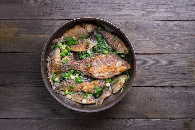 Сковорода с вкусным карасем на деревянном фоне