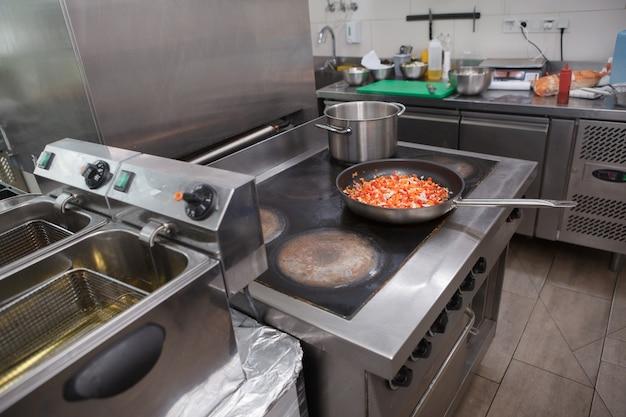 Сковорода с овощной смесью, готовящейся на плите на кухне ресторана, копией пространства